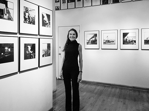 Margaret Morton at her gallery show in 2015, black and white photo of a woman standing in a gallery of photographs.
