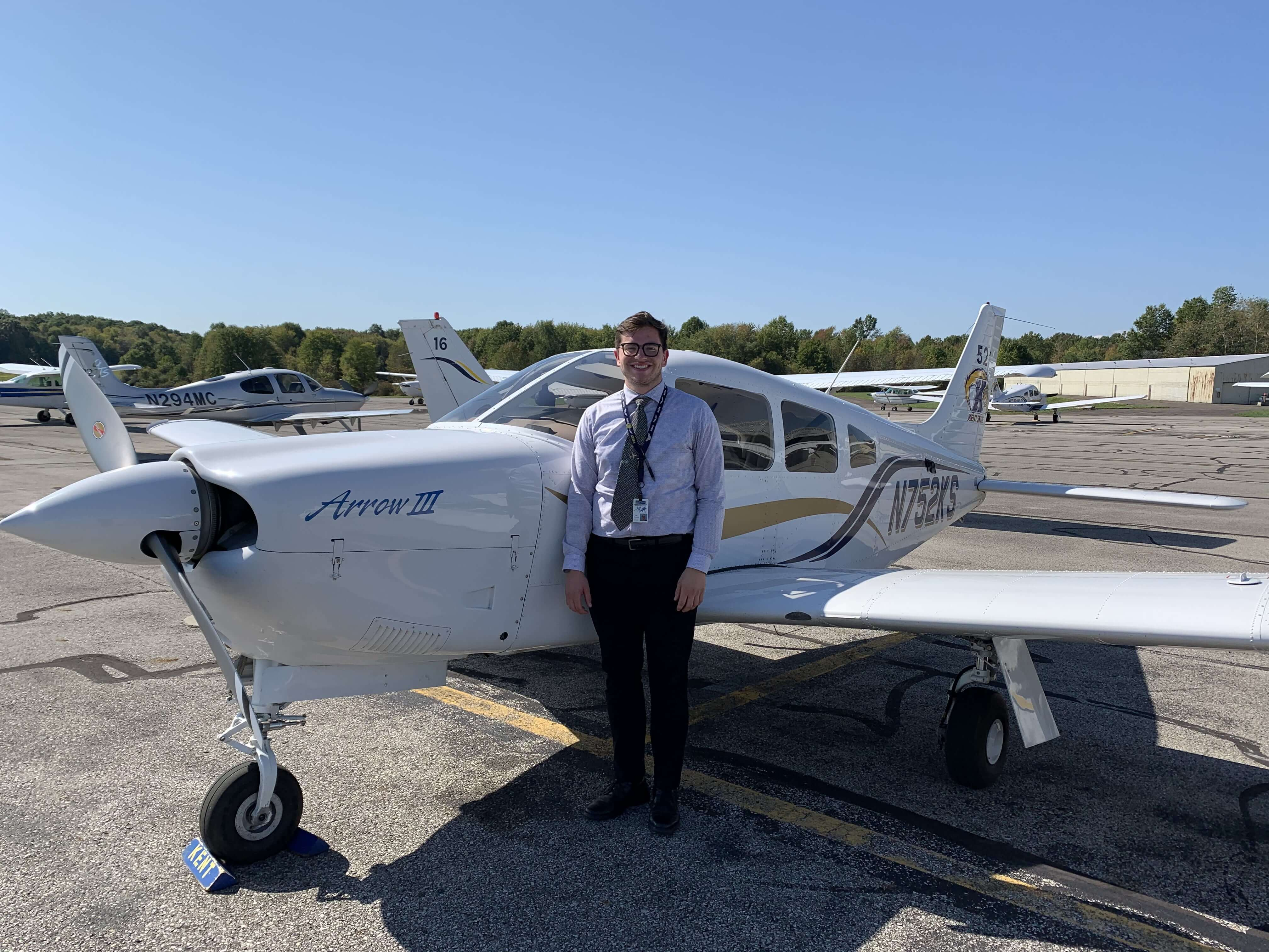 student in front of small plane