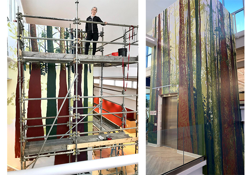 Eileen Dorsey painting an indoor mural of trees.
