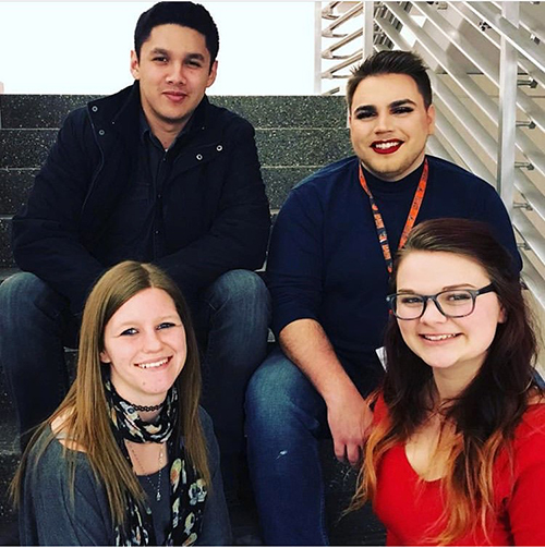 Four student officers for the NAEA student chapeter sitting on steps.