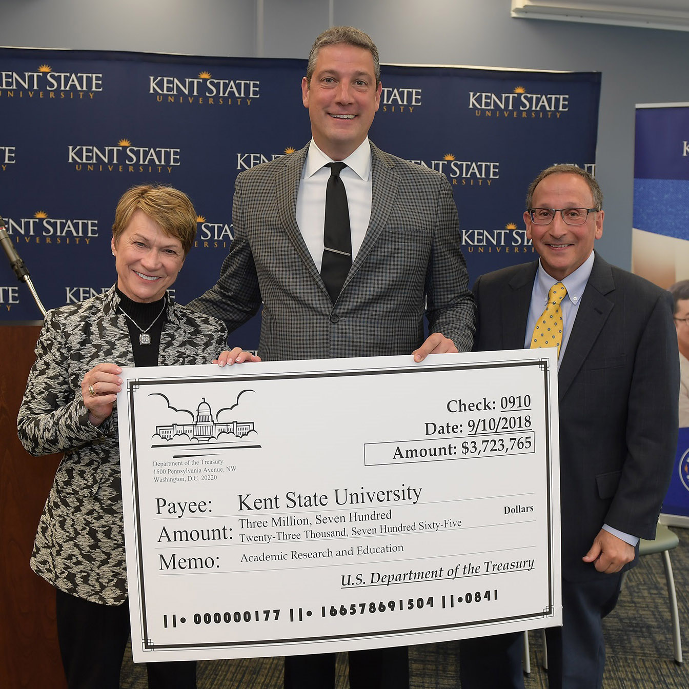 U.S. Rep. Tim Ryan (center) presents a giant check to Kent State University President Beverly J. Warren (left) and Kent State Vice President for Research and Sponsored Programs Paul DiCorleto (right).
