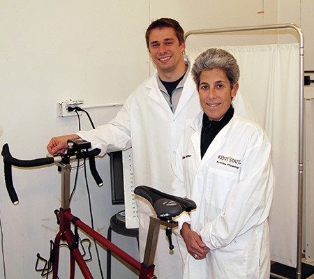 Kent State University's Adam Jajtner, Ph.D., and Ellen Glickman, Ph.D., stand next to an exercise bike in their research lab. The two exercise science/physiology faculty members will lead a study related to the use of probiotics and physical exercise.