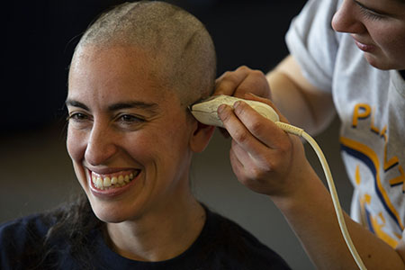 "Kent State employee Lisa Morde shaves her head to raise money for Habitat for Humanity in a campaign called ""Shave My Head to Put a Roof Over Her Head."""