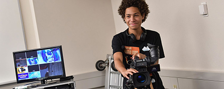 A Firestone Community Learning Center student learns how to operate a video camera during a class in Franklin Hall, home to Kent State University's School of Journalism and Mass Communication.
