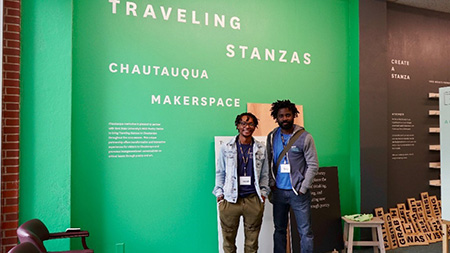 Kent State University students Isaiah Hunt and Sony Ton-Aimé pose at the Traveling Stanzas exhibit. Both students are the exhibit docents for two weeks.