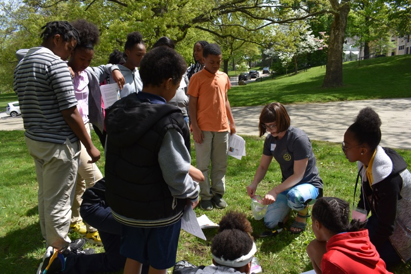 KSU Department of Geology graduate student Kortney Cole showing Schumacher Elementary School 6th grade students how to collect soil samples.