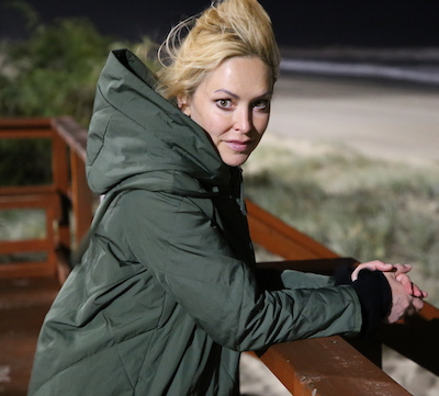 Rachel Armstrong, of Newcastle University (U.K.) stands near a beach at night.