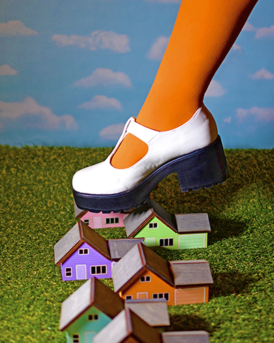 Artwork by Kate Rossello - a photograph of a foot with a white shoe and orange tights on stepping on tiny houses.