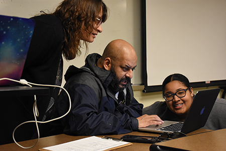 Karen Cunningham and Idris Kabir Syed, co-instructors of the course titled May 4, 1970, and Its Aftermath, help Rhea Hairston use digital archives of the May 4 Collection for her project involving Tent City.