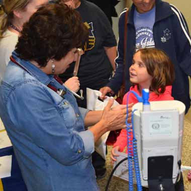 Dr. Mary Lou Ferranto, director of the nursing program, takes the pulse of a young girl.