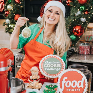 Leslie Srodek-Johnson in red apron and holiday hat, holding up Christmas cookie, smiling for the camera