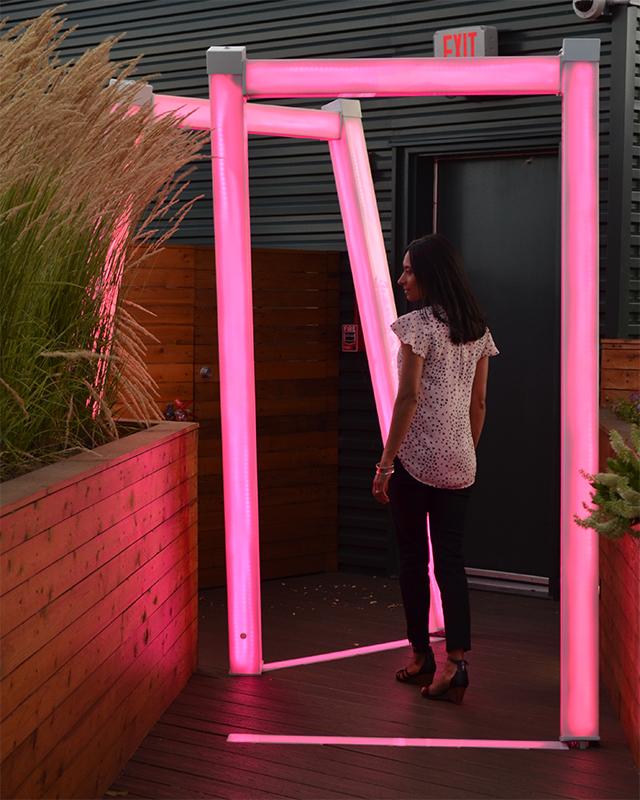 Scott Goss illuminated sculpture made of light-up tubing on a rooftop garden. A woman is standing inside of it.