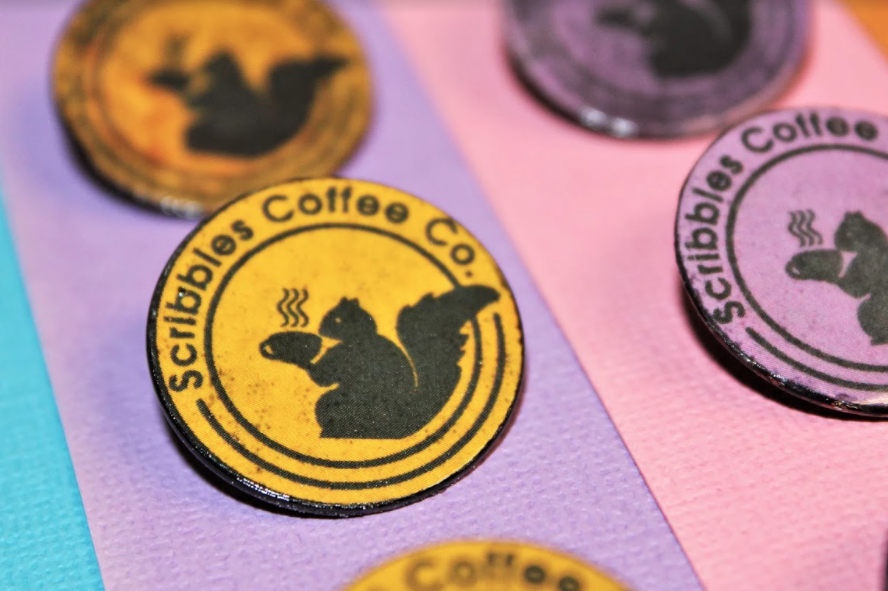 Round pins made by Danny Likar for Scribbles Coffee Co featuring a silhouette of a black squirrel drinking coffee.