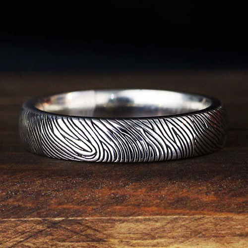 Silver ring with a fingerprint etched on the outside. Made by Jak Figler.