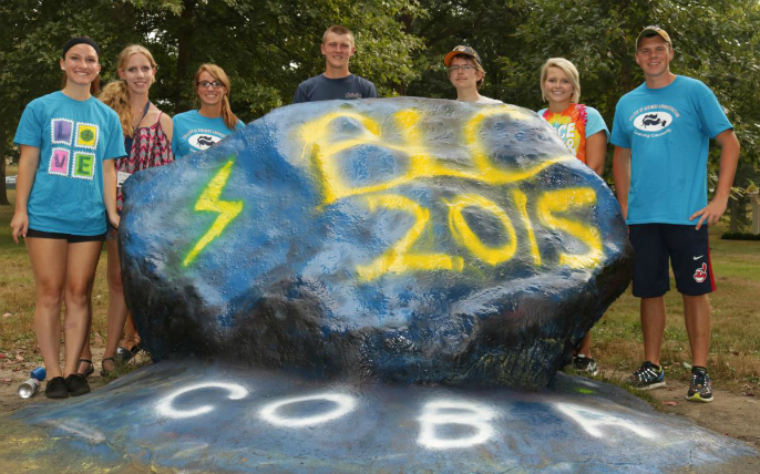 Students stand behind the front campus rock, which has been painted blue with gold letters B L C 2015.