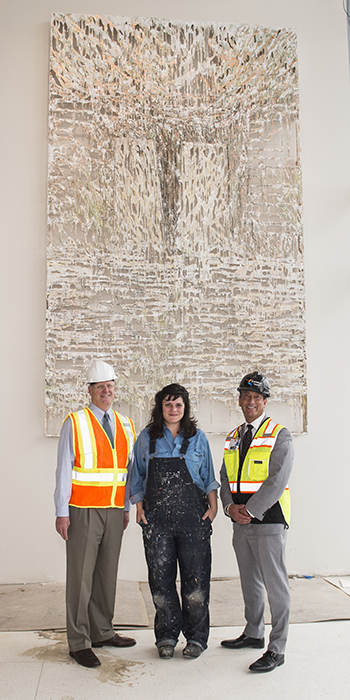 Alumna Diana Al-Hadid in front of her artwork installed at Summa Health Systems