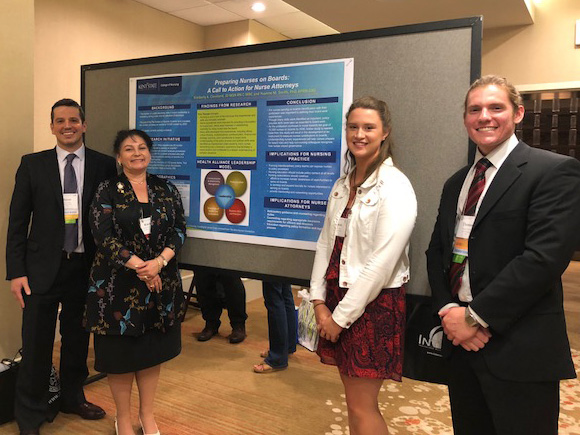 Jason Fisher, Kim Cleveland, Sarah Kearney, and Thomas Watral stand next to their collaborative poster presentations at the 2018 TAANA Conference.