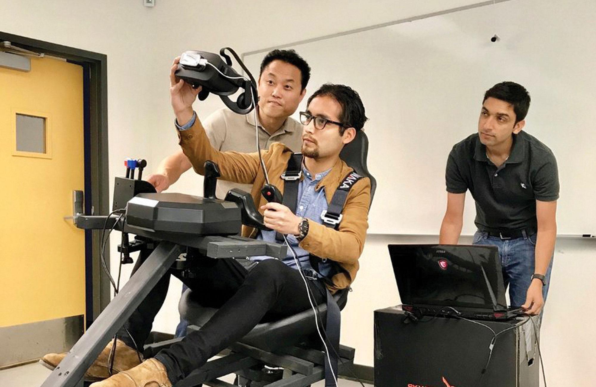Dr. Jong-Hoon Kim, Irvin Steve Cardenas, and Dr. Gokarna Sharma check out the ImmersiFLY flight simulator