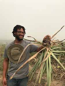 Christopher Thompson holding a pineapple plant during his internship in Ghana