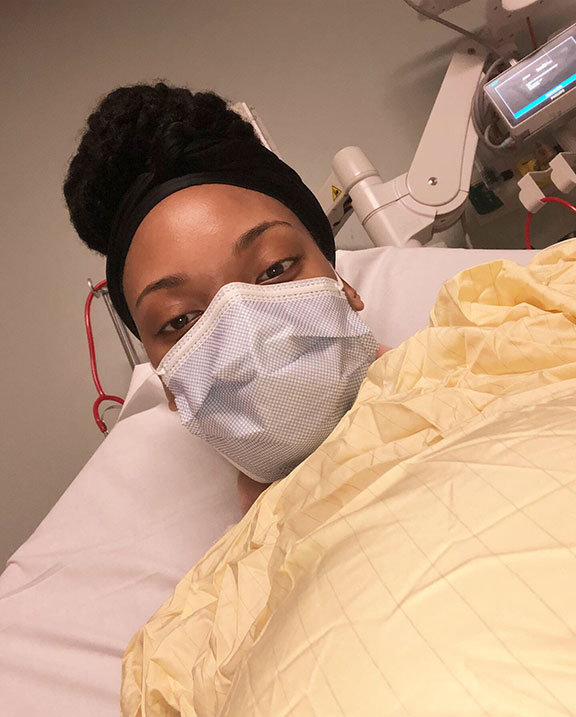 A selfie of Jones wearing a face mask and hospital gown while laying on a patient bed in the emergency room.
