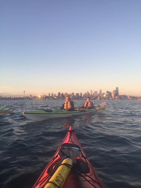 Kathleen Norman, marketing, communication and public relations director for the College of Nursing, is pictured kayaking with her son on the Puget Sound at sunset with Seattle in the background.
