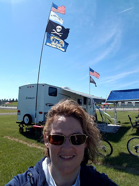 Kerry Angle, senior business manager for the Kent Student Center, proudly flies the Kent State flag (in the background) during her yearly vacation to the Michigan International Speedway for the annual June NASCAR series race week.