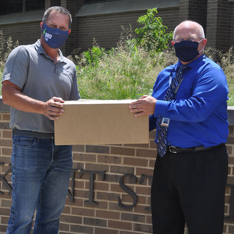 Matt Zines, program engineer at Ventra Salem and a KSU alum, hands over a carton of face shields to Dr. David Dees, dean and CAO of the Columbiana County campuses.