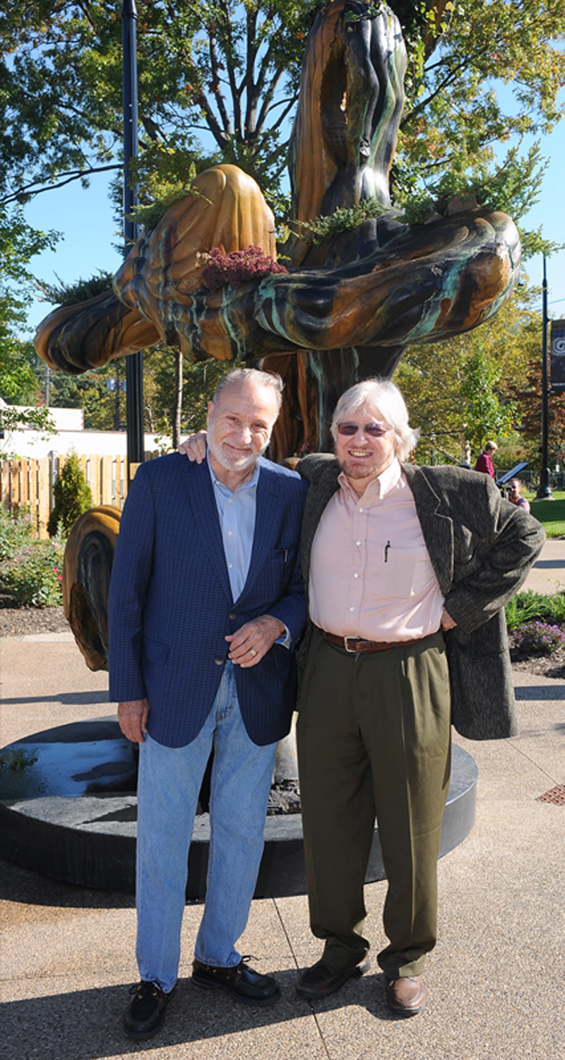 "Wick Poetry Center co-founders and brothers Walter (left) and Robert Wick (right) enjoy a moment in the newly dedicated Poetry Park in front of the sculpture ""Seated  Earth"" that Robert created."