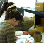 Archaeology students study ceramic jars from the Libben site, ca. 900AD, (KSU collections) during a lab.