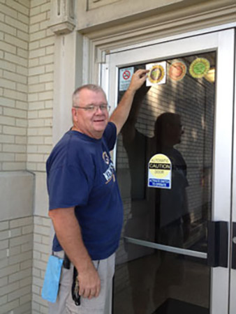Frank Fife, a maintenance employee at Kent State University at Salem, makes sure the third window decal is seen by all who enter the building.