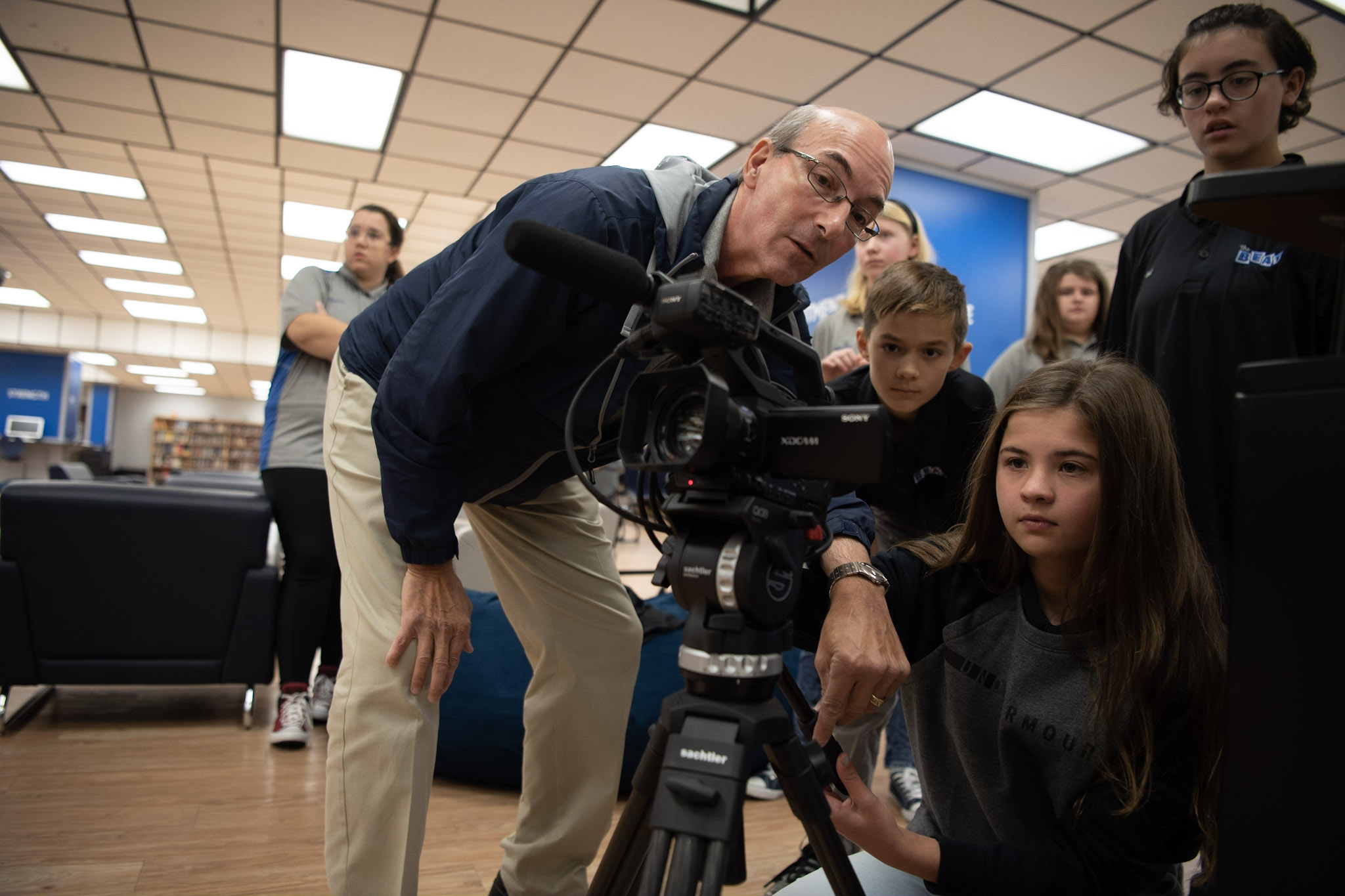 John Wasylko  shows one of The BEAT students how to adjust the height of a tripod.