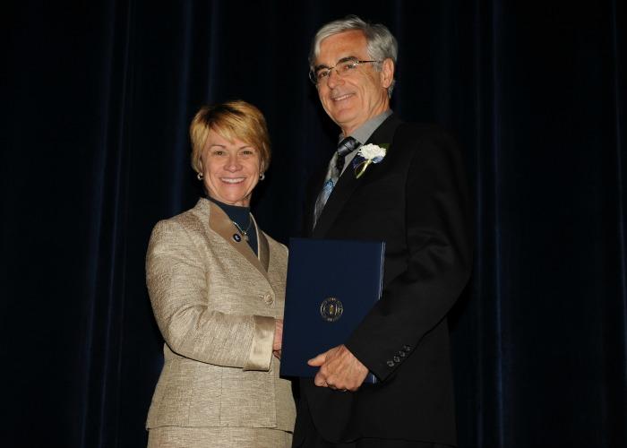 Thomas Bialke shakes hands with President Warren after receiving his Twenty-Year certificate