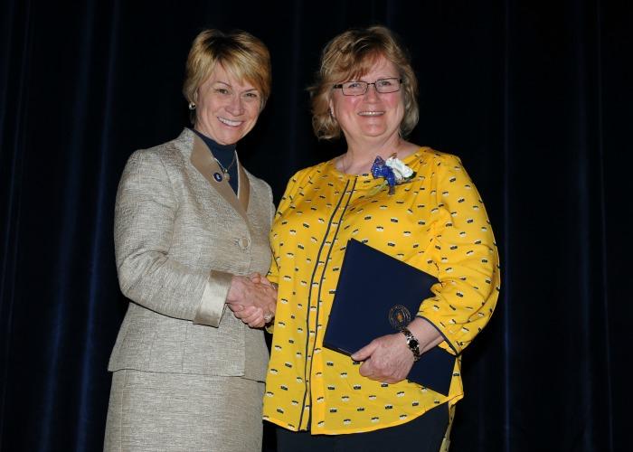 Inductee Elizabeth Brandt, shakes hands with President Warren after receiving her 20-Year certificate