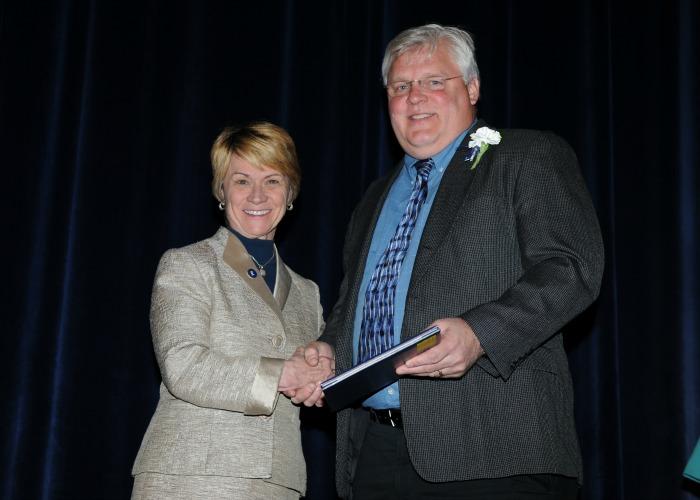 President Beverly Warren shakes inductee Karl Erdmann's hand after he receives his 20-Year certificate
