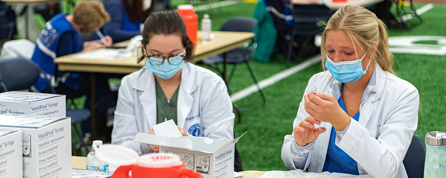 Medical professionals assist with vaccinations at the Kent State Field House
