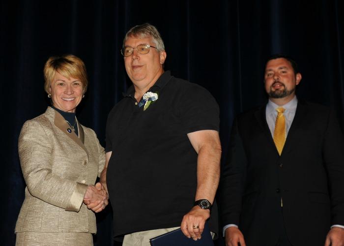 Inductee Steve Machamer shakes President Warren's hand while Jason Wearley looks on