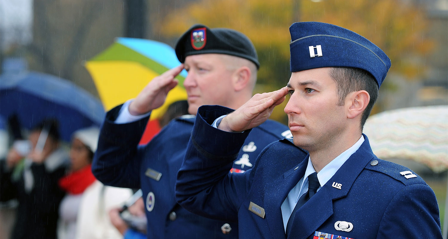 Members of the Kent State Air Force ROTC program salute as the American flag is raised during the university's annual Veterans Day observance.