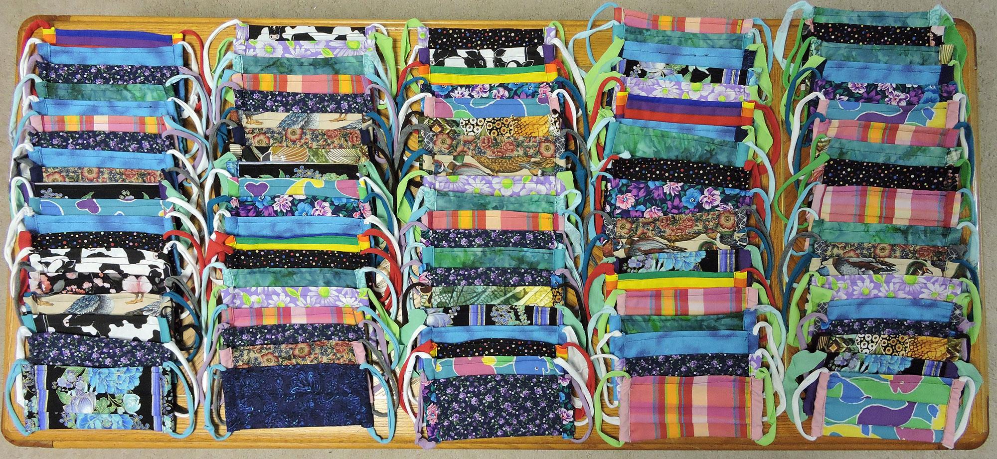 Handmade fabric masks laid out on floor