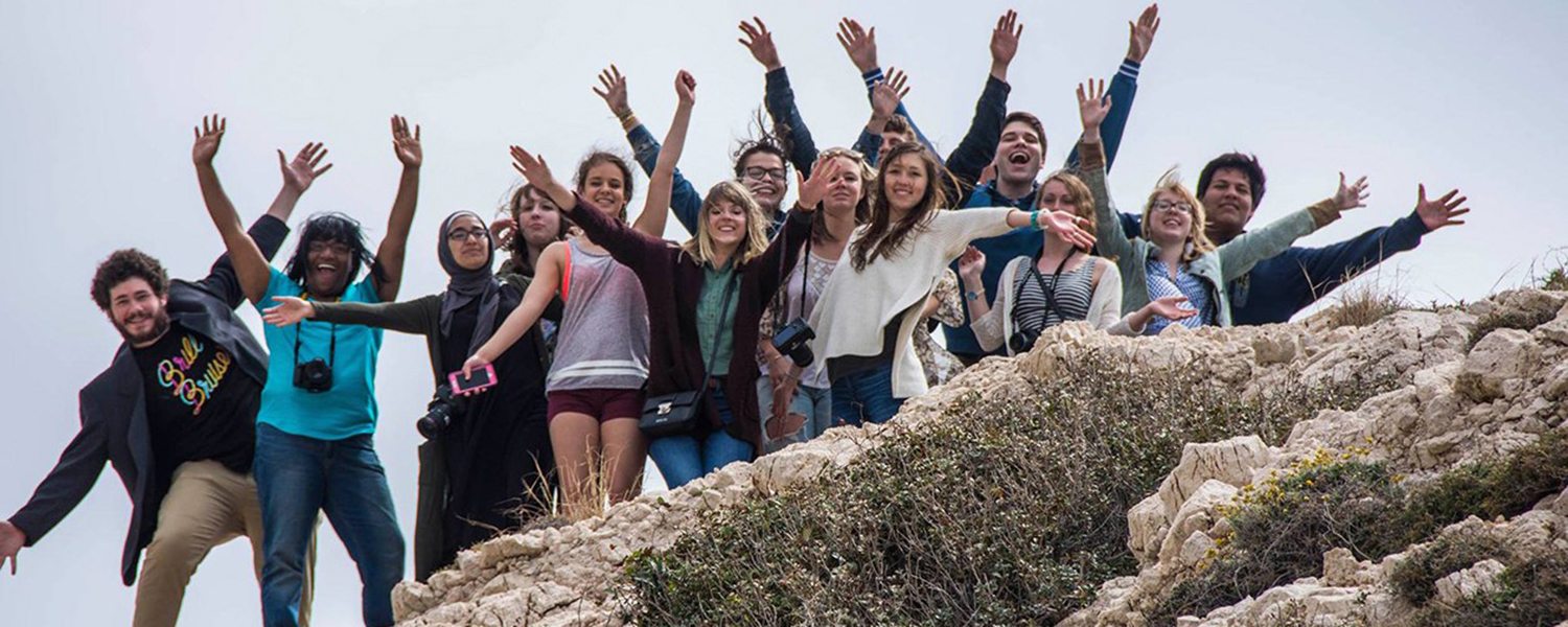 Students from the School of Journalism and Mass Communication's International Storytelling course smile for a group photo atop Aphrodite's Rock in Cyprus.