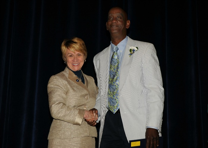 Inductee Maurice Peoples shakes hands with President Warren