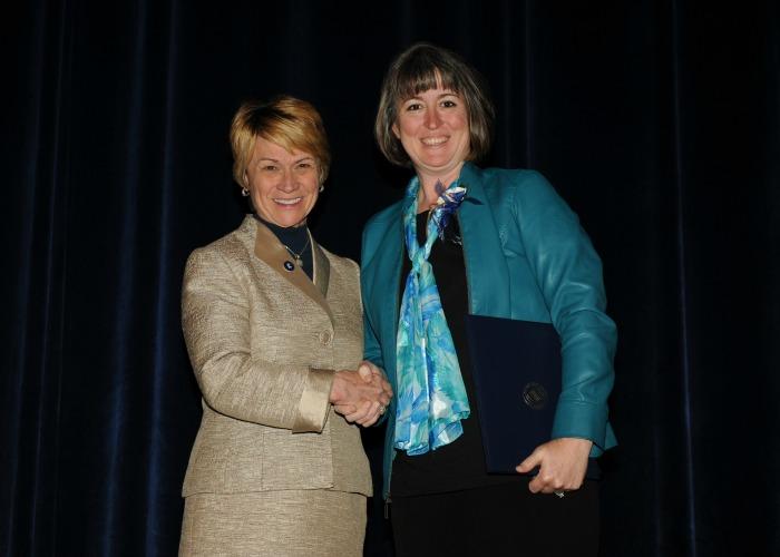 Inductee Sandi Randulic shakes hands with President Warren