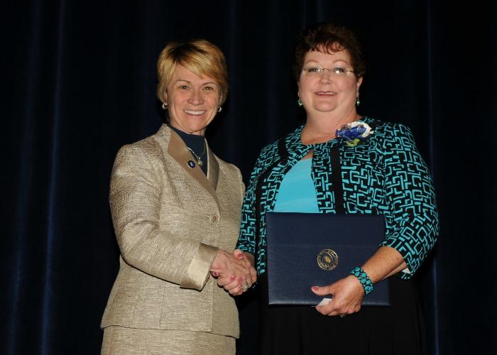 Inductee Brenda Shank shakes hands with President Warren
