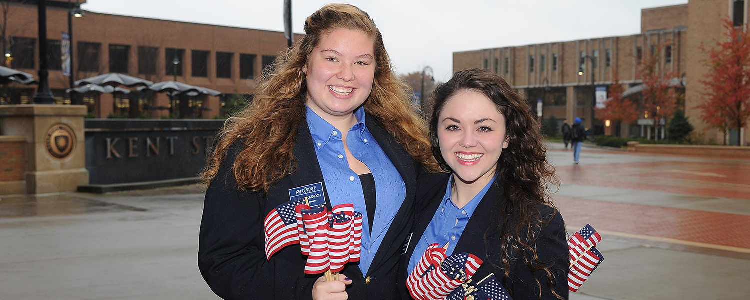 Student Ambassadors distribute American flags to staff, students and guests of the annual Veteran's Day ceremony on the Risman Plaza.