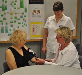Nursing students Judith Meanor and Becky Kirkner practice taking the blood pressure of Nursing Instructor Janet Peterson