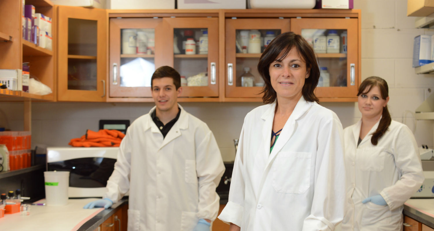 Gemma Casadesus-Smith, Ph.D., (center), an associate biology professor at Kent State, stands in a lab with two graduate students.