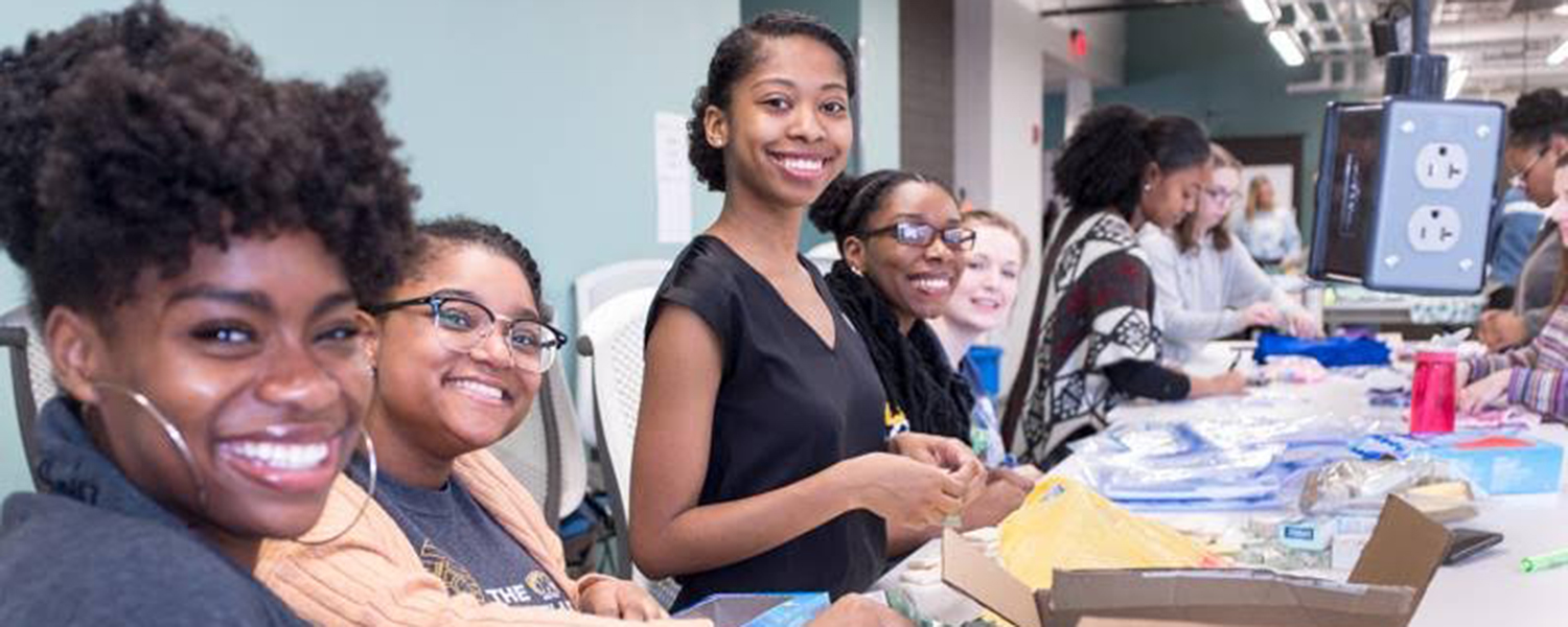 Members of the Kent State University community volunteer to put together feminine hygiene product kits for young women in developing countries.