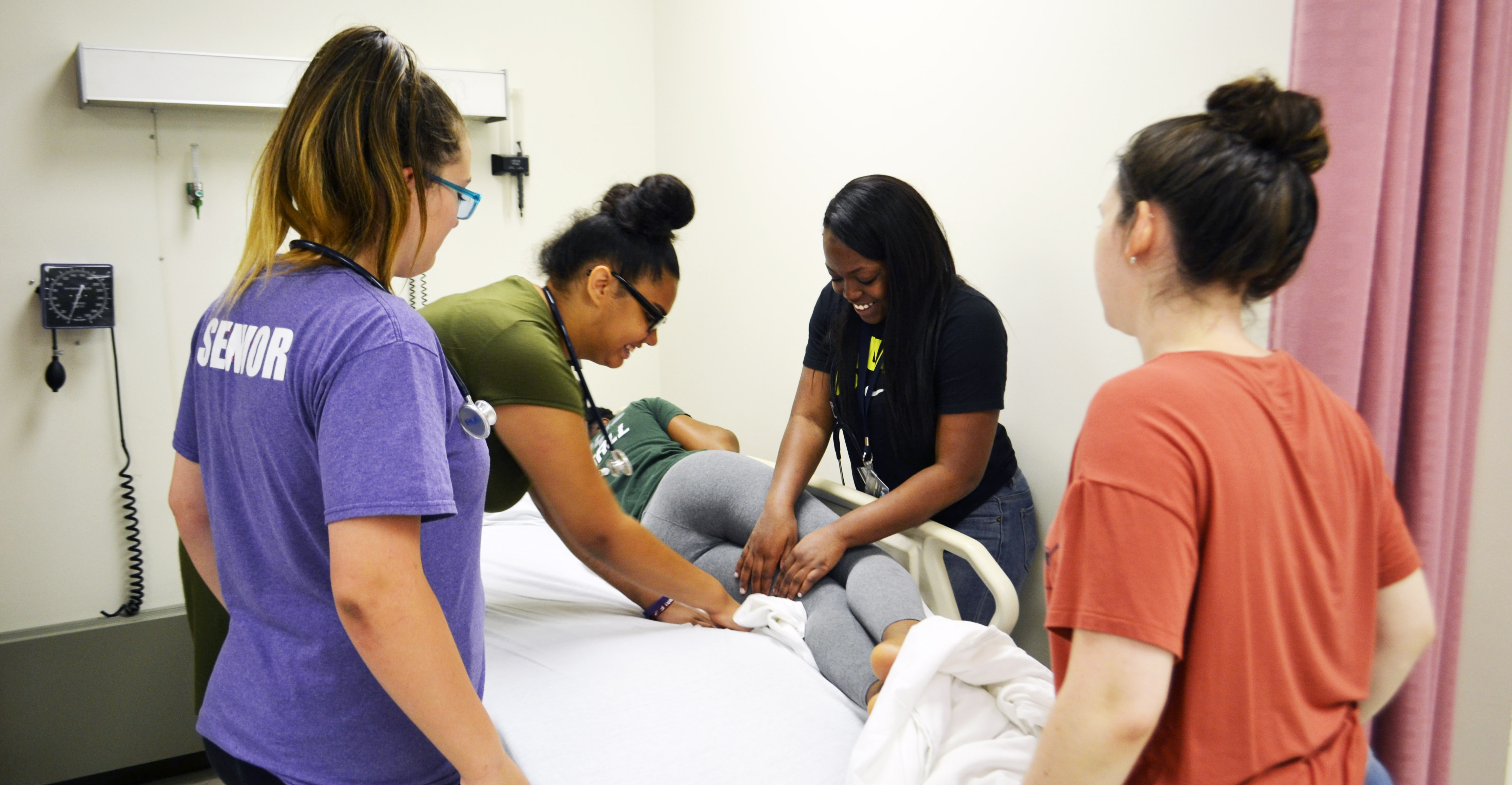 Senior nursing student, Rachel Benson (front, right), watches as Upward Bound students practice making a hospital bed occupied by a patient.