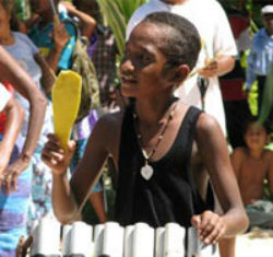 "A young boy, Pai Niu, plays ""bamboo drums"" at a religious festival on Taumako in 2007."