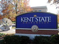 A Kent State University sign with the sculpture near Franklin Hall background