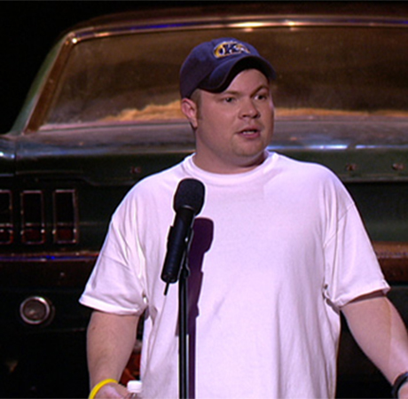 A standup comedian wearing a Kent State cap